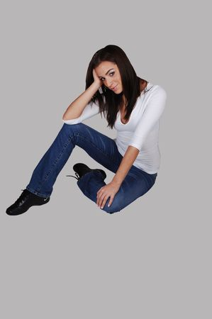 An young pretty woman in jeans and black boots, smiling and sitting on the floor, for light gray background. photo