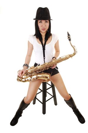 A beautiful Chinese woman with her saxophone on her lap, sitting on a chair in the studio for white background.  photo