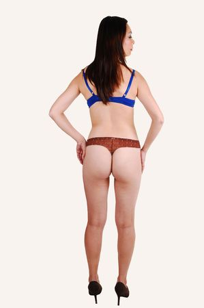 A slim young Chinese woman in blue and brown underwear standing in  the studio on high heels from the back, on white background. photo