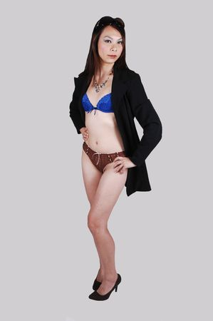 A slim young Chinese woman in blue and brown underwear and a black  jacked standing in the studio on high heels, on light gray background. photo