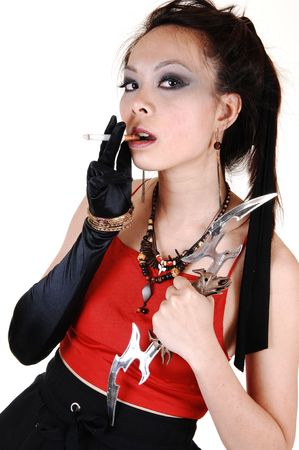 A young Chinese woman with black cloves and a red top standing in the studio with her slim body and smoking a cigarette, for white background. photo
