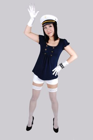 jacked: A smiling young Chinese woman in white shorts and white stockings,  navy blue jacked and white cloves, standing in the studio for white background.