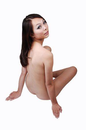 mujer desnuda sentada: Una mujer desnuda bastante China sentado con su espalda a la c�mara y mirando sobre su hombro, sobre fondo blanco.