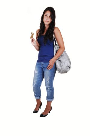 A young woman with long brunette hair, thinking to spend or not, with her credit card in her hand and a bag over her shoulder, for white background.  photo