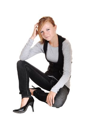 A young blond red haired woman in high heels and gray jeans sitting on the floor, on white background.