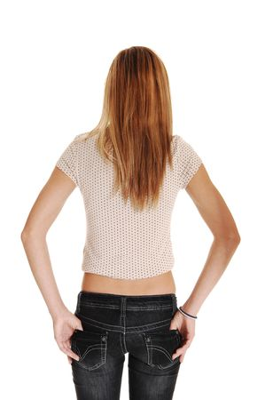 hand: A young blond red haired woman in gray jeans and a beige sweater standing from the back for white background.