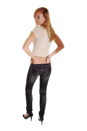 A young blond red haired woman in gray jeans and a beige sweater standing from the back and looking over her shoulder, for white background.  Stock Photo - 7838096