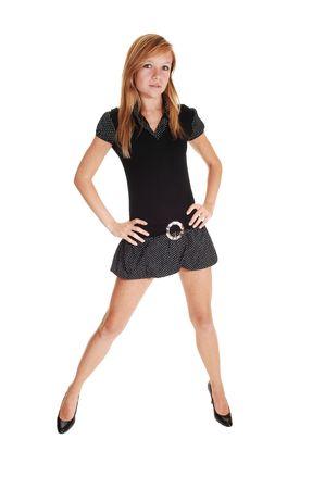 beine spreizen: Eine h�bsche junge Frau in einer kurzen schwarzen Kleid und high Heels in Studio mit ihren Beinen stehen zu verbreiten, auf wei�em Hintergrund.  Lizenzfreie Bilder