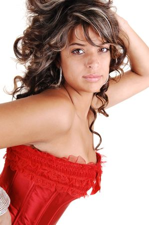 Closeup of a beautiful young woman in a red corset and long brunet curly hair for white background. photo