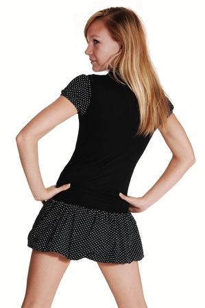 looking over shoulder: A young pretty woman with long red, blond hair standing in a short black  dress from the back, in the studio for white background. Stock Photo