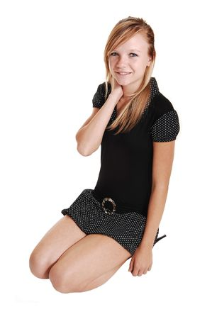 A young blond red haired woman in high heels and black short dress sitting on the floor, on white background.