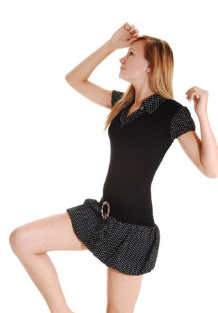 An young woman in a black short dress and red blond hair, dancing in the studio for white background.  Stock Photo