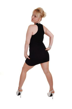 A young pretty blond woman in a black evening dress and silver heels, standing in the studio, shooing her nice body, over white background. photo
