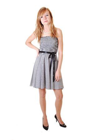 Een jonge en mooie blonde vrouw in een zwarte witte jurk en zwarte hakken, staan in de studio, shooing haar mooi lichaam, over witte achtergrond.  Stockfoto - 7992561