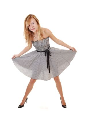 A young pretty blond woman in a black white dress and black heels, standing in the studio, shooing her nice body, over white background. photo
