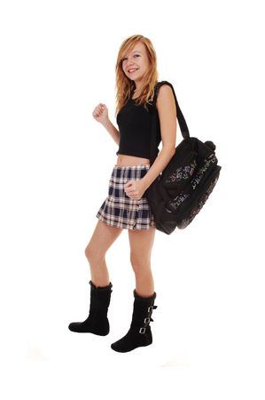 A young teenager in black boots and a short skirt with her back bag over her shoulder on the way to school, on white background. Фото со стока