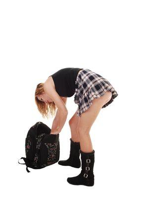 falda corta: Una joven adolescente en botas negras y una falda corta con su bolsa de espalda en el suelo y buscando algo, sobre fondo blanco.  Foto de archivo