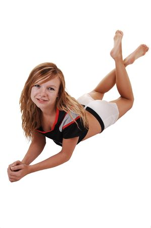 A young teenage soccer girl lying on the floor in her uniform, with her legs crossed, for a portrait in the studio, over white background.