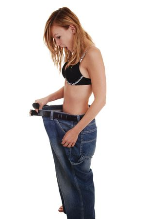 A slim teenage girl in a black bra and a very big jeans, after she last so much weight, is very surprised, for white background. Imagens