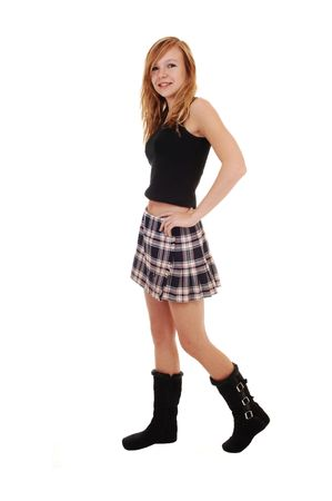 A young teenager in a skirt and black boots  standing from the front, and looking into the camera,  for white background. photo