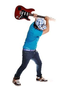 A teenage boy in jeans and s blue sweater is mad at his guitar and like to smash it on the floor, for white background.