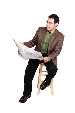Een man van het midden leef tijden zitten en lezen van de krant in jurk broek en een bruine jas en groene trui, voor witte achtergrond.