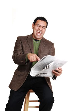 An middle ages man sitting and reading the newspaper and having fun, in dress pants and a brown jacket and green sweater, for white background. photo