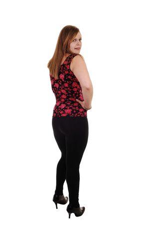 An pretty blond woman in black tights and a red vest and high heels standing in the studio, for white background. 免版税图像
