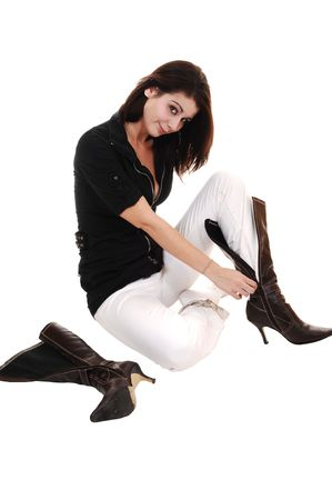 A young pretty woman sitting on the floor in white pants and a black  jacket and putting on her long boots, on white background.