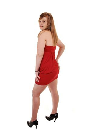 A young pretty blond woman in a red evening dress and black heels, standing in the studio, looking over her shoulder, over white background. photo