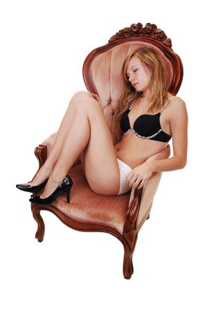 A young blond woman, sitting in a pink armchair in her underwear and black heels and bra and sleeping, for white background.  photo