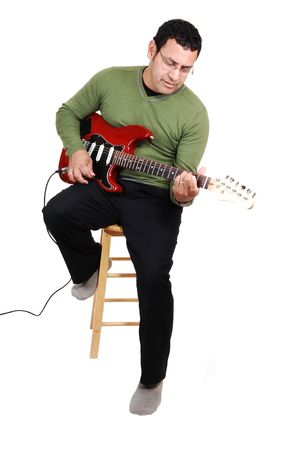 A middle aged man sitting in the studio, playing his guitar in dress pants and green sweater, for white background. photo