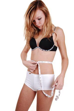 white panties: Eine junge pretty blond Frau in ein schwarzer BH und wei� H�schen measuring her Waist sehr schlank, f�r wei�en Hintergrund.