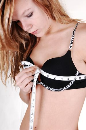 A young blond woman in a black bra and slim body, measuring her breasts, for white background. photo