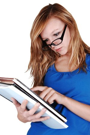 A young blond woman with glasses, reading in the books she has in her hand in a blue sweater standing for white background in the studio. Stock Photo - 8174397