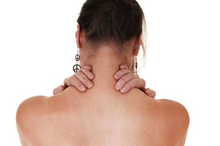 woman back of head: A woman standing with her back to the camera and massage her neck to ease the pain in her neck and shoulder.