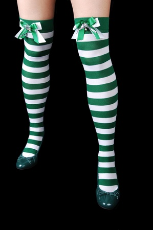 The beautiful legs of a woman in green and white stripes, with green heels for black background. photo