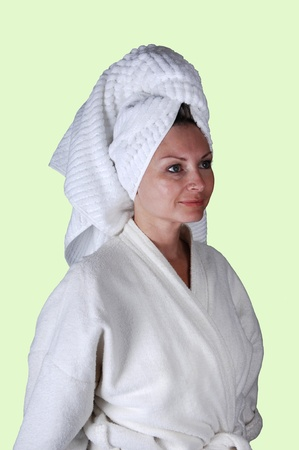 A middle aged woman in a white bathrobe and a towel around her hair standing in the studio looking into the camera. photo