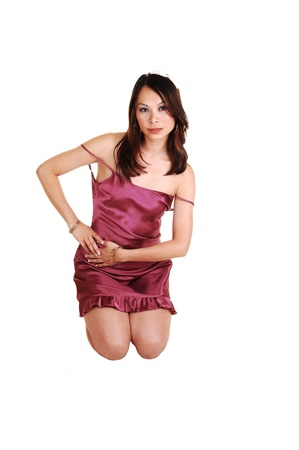 A young woman kneeling in the studio in a burgundy short night gown with brunette hair for white background.