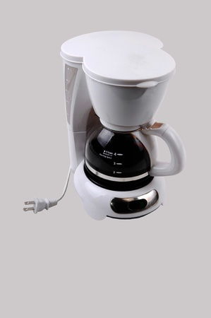 coffeemaker: A white small four cup coffeemaker, with coffee in, for light gray background.  Stock Photo