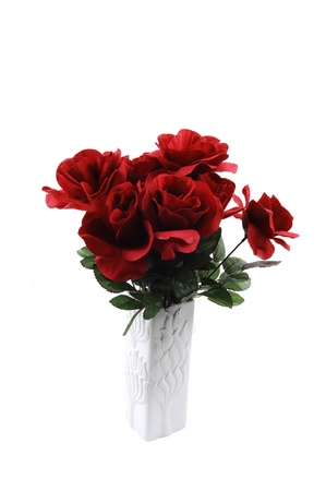 A bunch of red silk roses in a white vase for white background.
