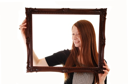 empty space: An young woman with long red hair holding a picture frame, in a black dress, with empty copy space in the frame, on white background.