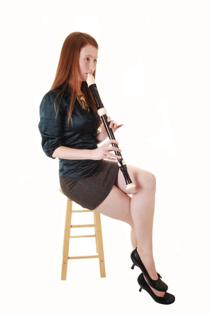 A young woman with long red hair sitting in a green blouse and brown skirt on a chair and playing the flute, for white background. photo
