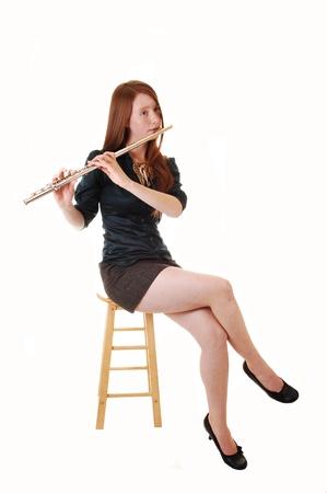 長い赤髪グリーンのブラウスと茶色のスカート椅子の上に座っているとの白背景のフルートを持つ若い女性。