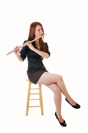 A young woman with long red hair sitting in a green blouse and brown skirt on a chair and playing the flute, for white background.