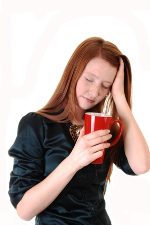A young woman with long red hair with a headache holding her head and a mug of coffee, in a green blouse for white background. photo