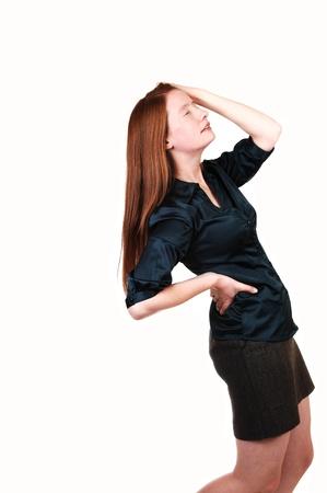 Een jonge vrouw met lang rood haar bedrijf haar rug voor pijn met haar rug, in een groene blouse en bruin korte rok voor witte achtergrond.