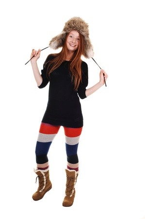 winter fashion: A pretty woman with long red hair in colorful tights, a black sweater  and a fur hat and brown boots smiling for a portrait for white background. Stock Photo