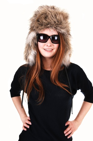 The portrait of a young woman with long red hair, sunglasses and a fur hat and a black sweater smiling into the camera, over white.