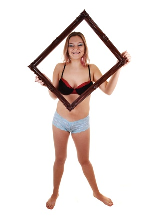 A young woman in blue panties and a black bra, holding a picture frame up over her head and chest, standing bare feet for white background. photo